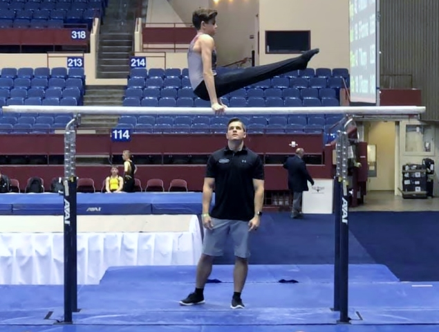 Will Weiper, Junior Development Div. 1 Level Competes On The Parallel Bars  Under The Watchful Eyes Of Coach Ryan Turney.